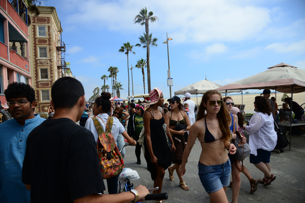 People walk on the Venice Beach boardwalk on August 4, 2013. The Los Angeles City Council voted Tuesday to ban motorized scooters from the popular walkway after a spate of collisions with pedestrians.