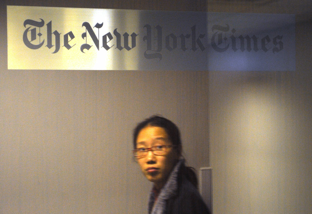 A woman walks past the New York Times office in Shanghai on October 30, 2012. Lawyers for relatives of Chinese Premier Wen Jiabao have hit back at an 'untrue' New York Times article which alleged the family has accumulated vast wealth, a report said.