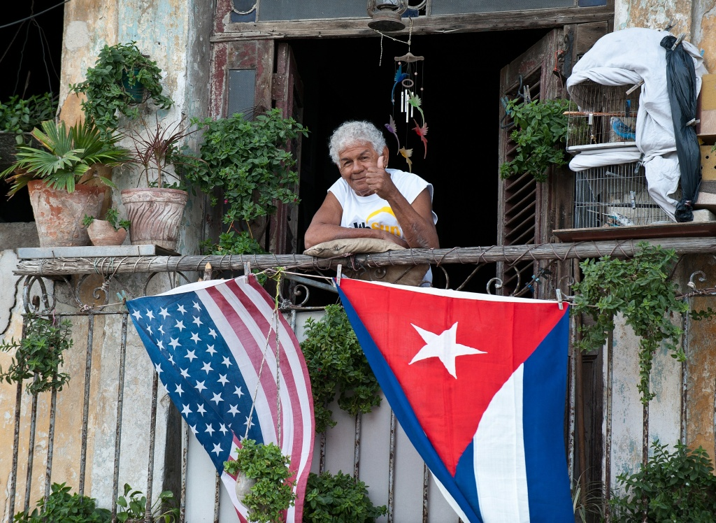 A Cuban gives the thumbs up from his balcony decorated with the US and Cuban flags in Havana, on January 16, 2015. The United States will ease travel and trade restrictions with Cuba on Friday, marking the first concrete steps towards restoring normal ties with the Cold War-era foe since announcing a historic rapprochement.