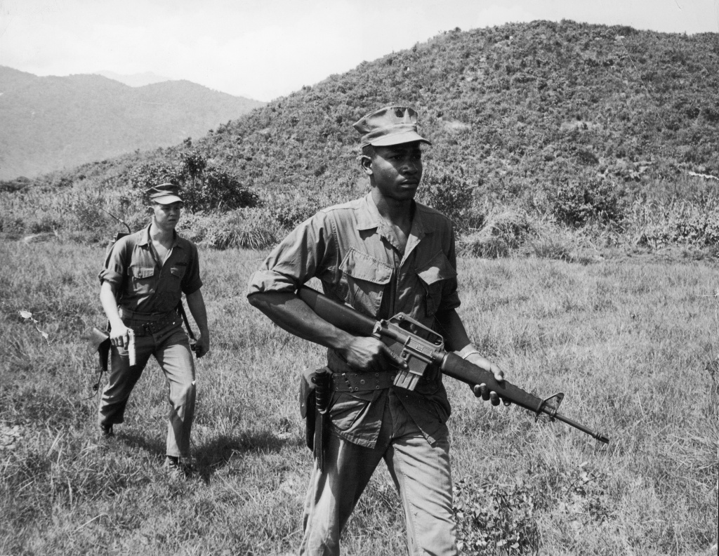 Soldiers Lance Corporal Murphy (R) and Sergeant Paige patrol a jungle area, carrying a rifle and a pistol during the Vietnam War, 1960s.