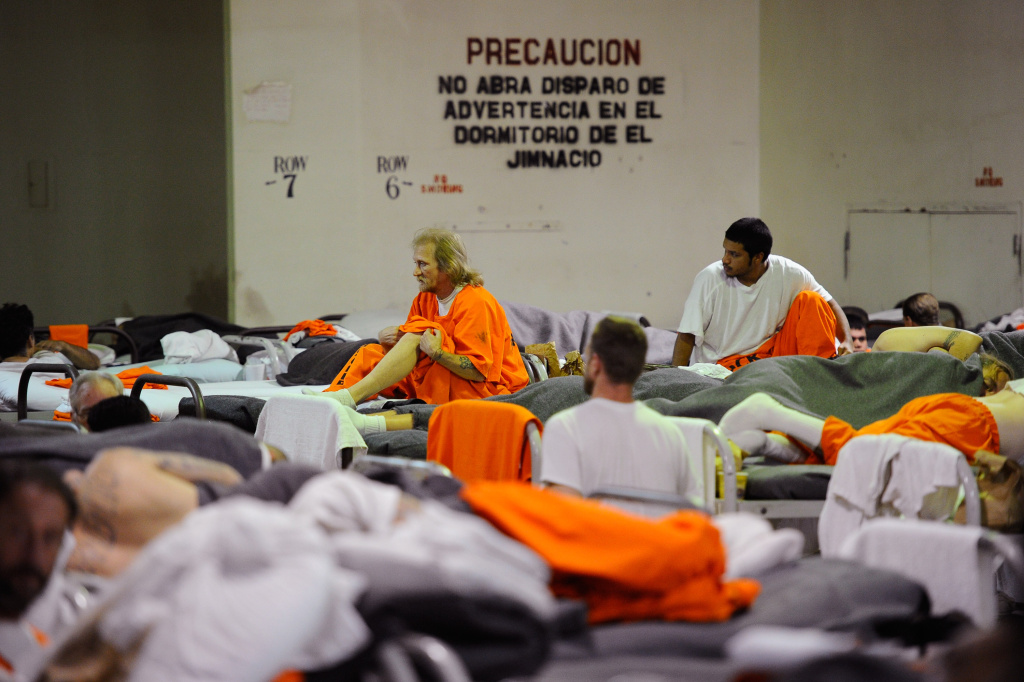 Inmates at Chino State Prison, which houses 5500 inmates, crowd around double and triple bunk beds in a gymnasium that was modified to house 213 prisoners on December 10, 2010 in Chino, California.