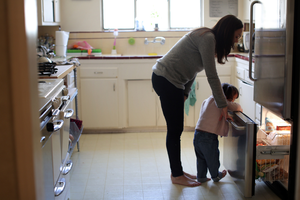 Foster parent Tamar Chateff and 2-year-old Charlotte look in the fridge for an afternoon snack while at home on Friday, March 28.