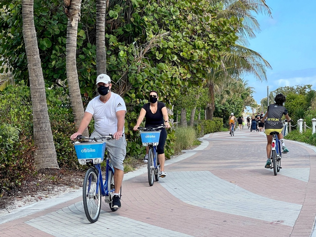 People bike along the beach in Miami on Dec. 20, 2020.