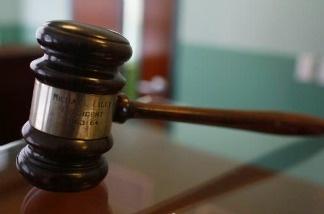 A judges gavel rests on top of a desk.