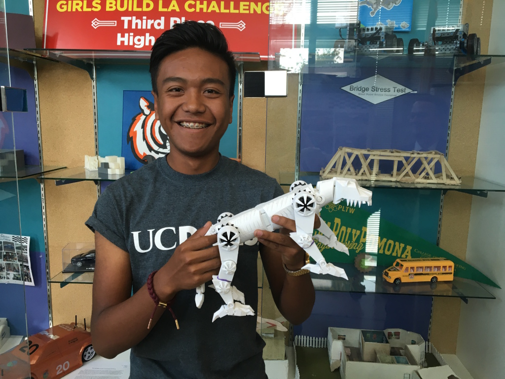 "José Rodríguez, 17, a senior at STEAM Legacy High School in South Gate, poses with a 3D-printed model of the school's mascot, the ""Tigerbot."" He plans to attend UC Berkeley in the fall."