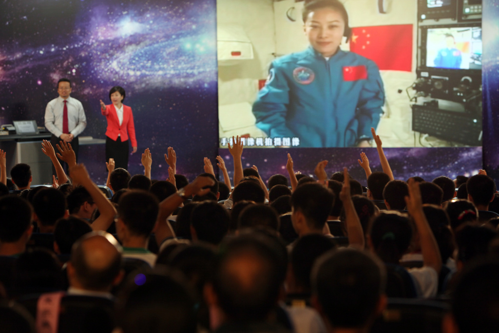 Students gathered in a school in Beijing raise their hands to ask Chinese female astrounaut Wang Yaping questions as she delivers a lesson to them from Tiangong-1 space module in the morning of June 20, 2013.
