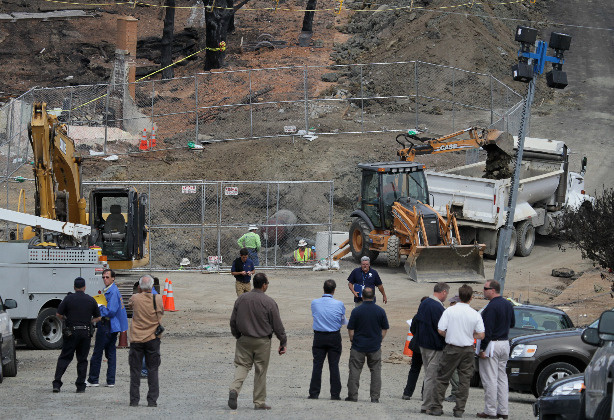 Officials look on as Pacific Gas & Electric workers excavate the crater at the epicenter of a deadly gas main explosion September 13, 2010 in San Bruno, California. State regulators have ordered Pacific Gas & Electric to inspect all of their gas lines following a deadly blast that destroyed thirty eight homes, severely damaged dozens more and killed at least four people in a San Bruno, California neighborhood near San Francisco International Airport on Thursday evening.
