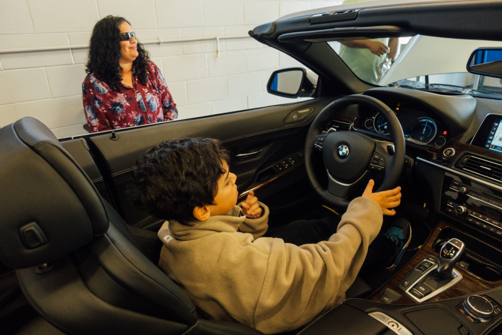 Lizzie Lopez and son check out a car at the opening of the BMW MSTEP at Marine Corps Base Camp Pendleton.