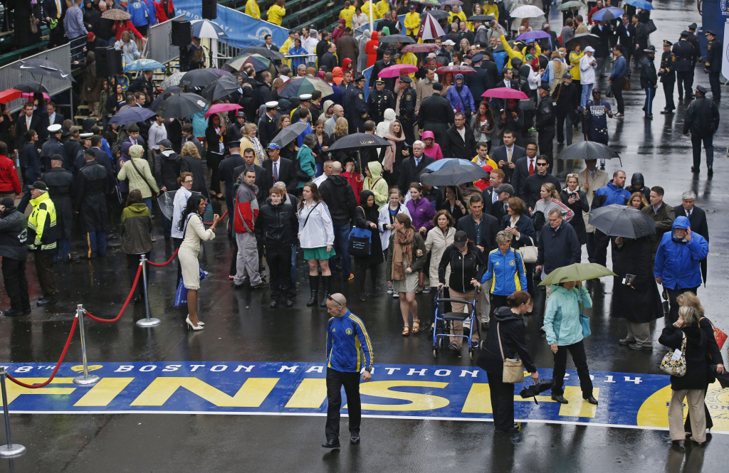 Family members, friends and survivors of the 2013 Boston Marathon bombing walk to the finish line after a remembrance ceremony on Boylston Street in Boston, Tuesday, April 15, 2014. The area was evacuated Tuesday when two unattended backpacks were found near the finish line.