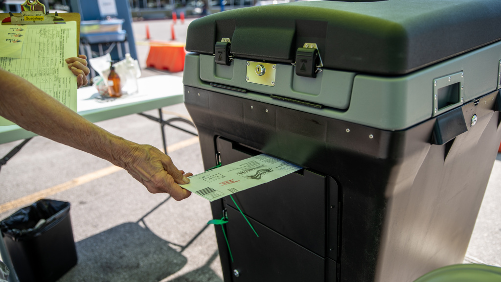 A federal appeals court is allowing Texas Gov. Greg Abbott's limit of one absentee ballot drop-off spot per county to stand, saying voters have many options. Here, a worker puts a ballot into a lockbox at a drive-through mail ballot hand delivery center in Austin.