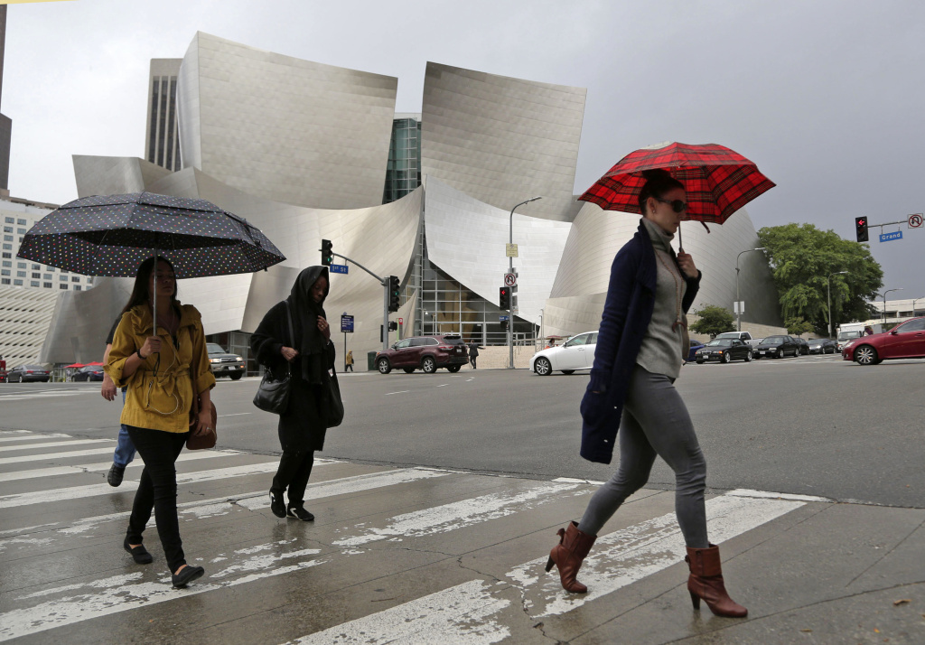 Umbrellas protect people from rain as they walk past the Frank Gehry-designed Disney Hall in downtown Los Angeles as one in a series of storms passes through Southern California. File photo from Oct. 28, 2016.
