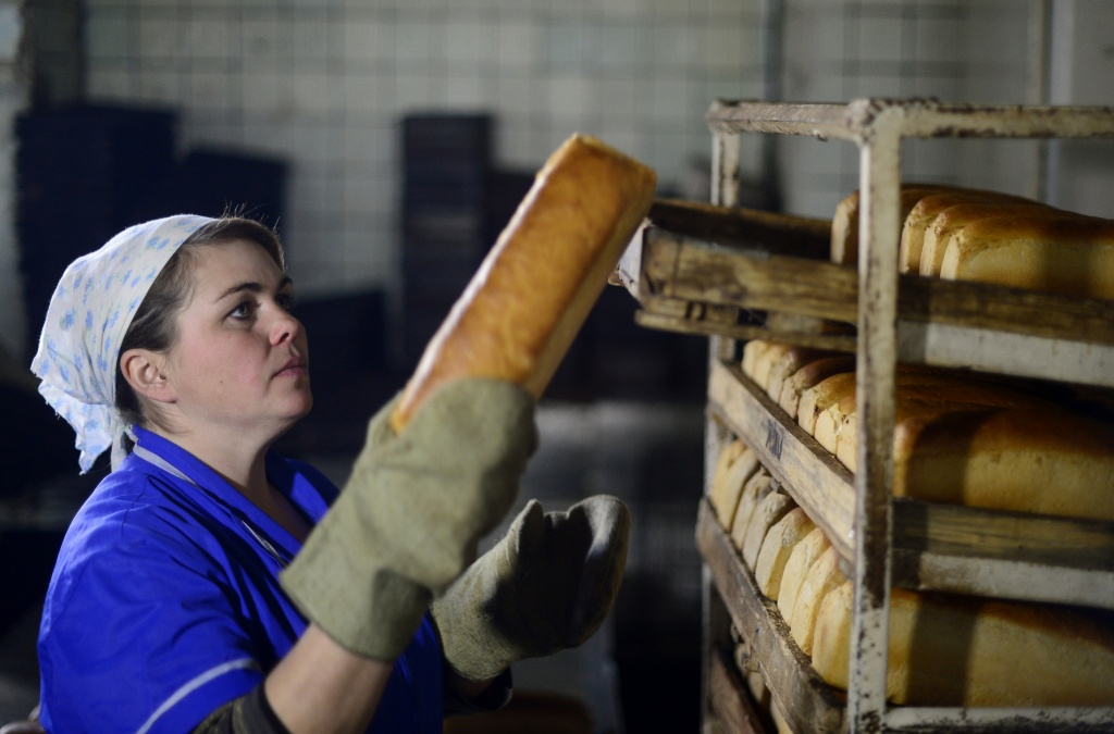 A worker in a bread factory stacks loaves of bread in Debaltseve, Ukraine on March 9, 2015.  The city, captured from Ukrainian troops by soldiers of the self-proclaimed Donetsk People's Republic on February 18, is slowly coming back to life.
