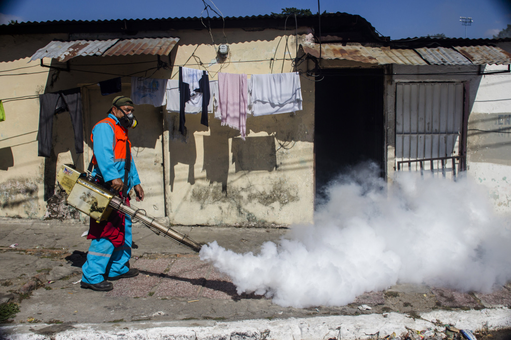 A city worker fumigates to combat the Aedes Aegypti mosquitoes that transmit the Zika virus, at the San Judas Community in San Salvador, El Salvador, Tuesday, Jan. 26, 2016.  Worries about the rapid spread of Zika through the hemisphere has prompted officials in El Salvador, Colombia and Brazil to suggest women stop getting pregnant until the crisis has passed. (AP Photo/Salvador Melendez)