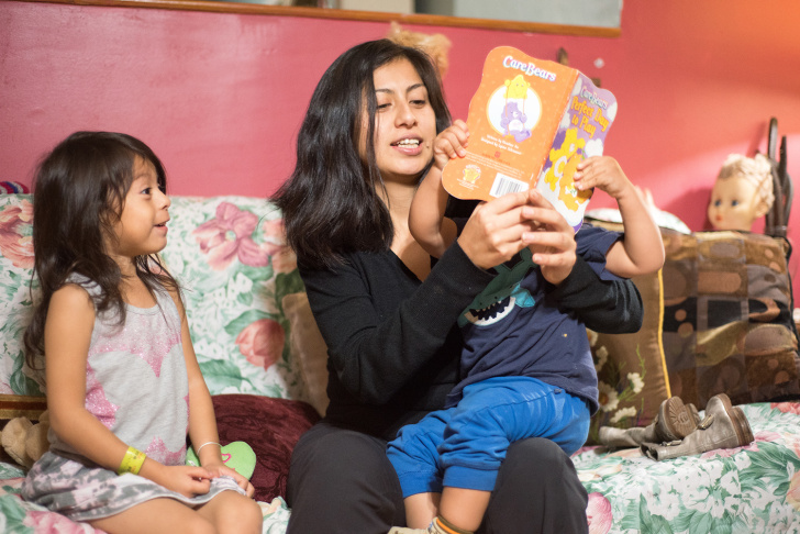 Sara Martín reading bedtime stories to her two kids. The single mom says taking them on two buses to get their vaccinations made it a challenge to keep the kids up to date with their shots.