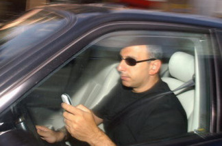 A man writes a text message on his mobile phone whilst driving in traffic.