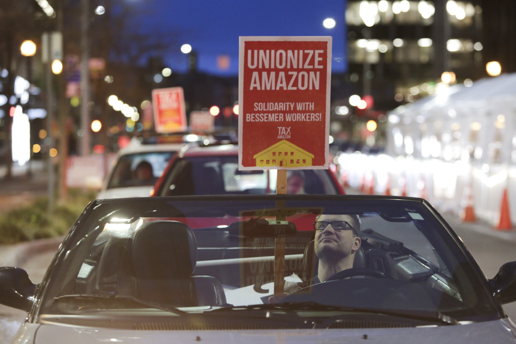 A man holds a sign in support of Amazon workers unionizing in Bessemer, Alabama as a convoy of cars circles the Amazon Spheres during a Tax Amazon Car Caravan and Bike Brigade event in Seattle, Washington on February 20, 2021.