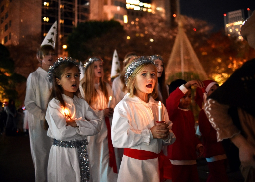 Children from the Swedish school in Japan sing Christmas songs before ice-made castles to celebrate the Saint Lucia Festival and Christmas at a hotel in Tokyo on December 11, 2014.