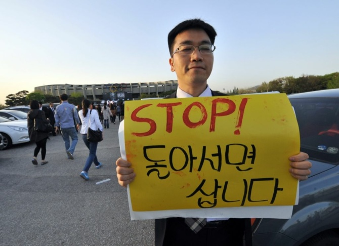 A protestors holds a placard against Lad