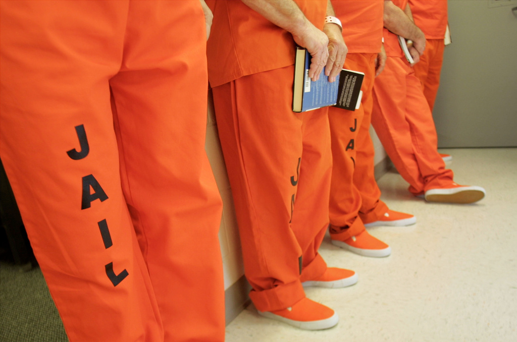 Volunteer inmates wear orange prison uniforms during an overnight stay at the new Cass County Law Enforcement Center. Civilians were to invited stay in the prison in order to work out potential bugs and test procedures.
