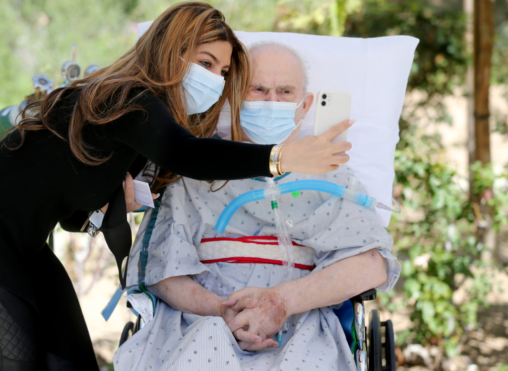 Alina Khachi takes photos as she reunites with her father Abdollah Khachi at Providence Holy Cross Medical Center's Sub-Acute Center in the Mission Hills neighborhood on March 22, 2021 in Los Angeles, California.