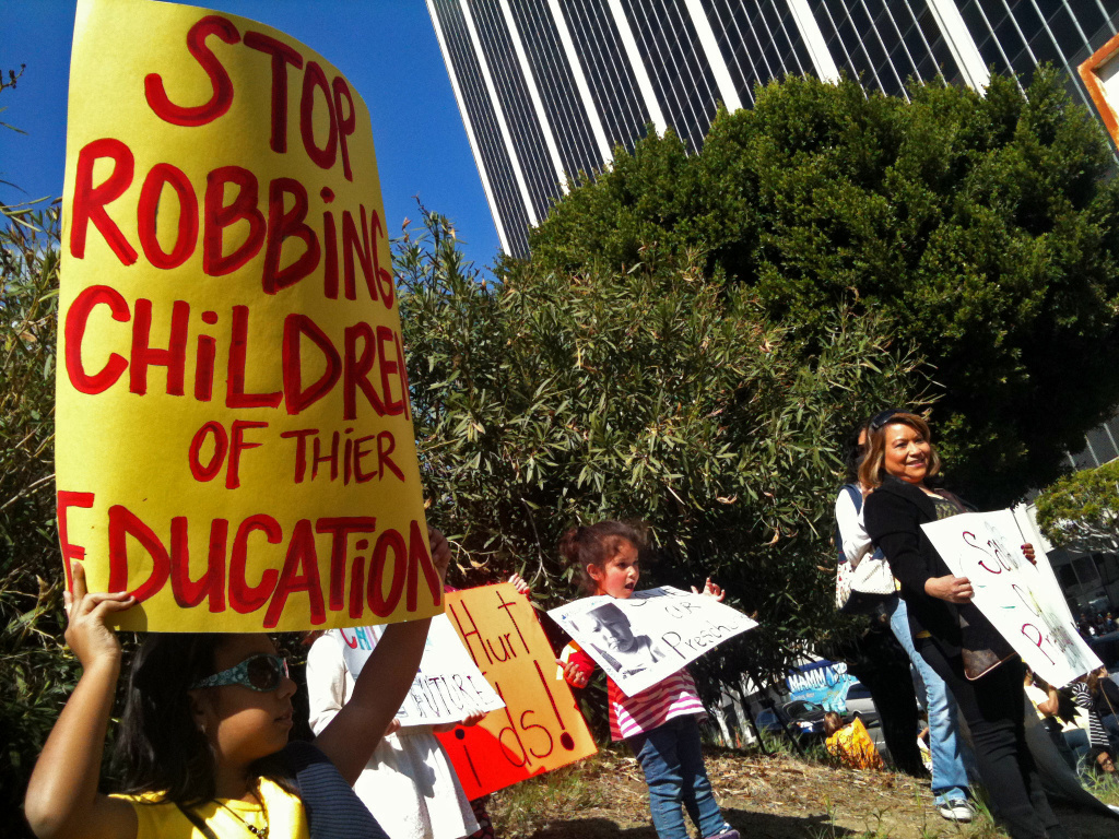 Several hundred people protested outside L.A. Unified headquarters earlier this year as the school board prepared to cut funding to preschool and adult education. The protests continue, made all the more tense by tens of thousands of pink slips the state has sent to teachers.