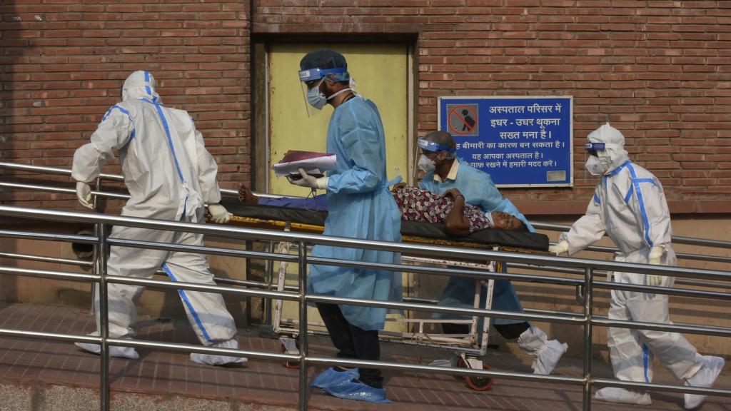 Medical professionals escort a patient into the the COVID-19 ward at Lok Nayak Jai Prakash Hospital in New Delhi on June 15.