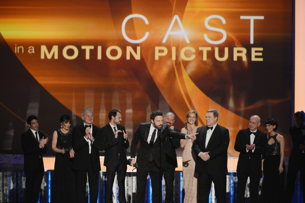 (L-R) Actors Chris Messina; Clea DuVall; Victor Garber; Christopher Denham; Ben Affleck (speaking); Kerry Bishe; John Goodman; Tate Donovan; and Alan Arkin accept the award for Outstanding Performance by a Cast in a Motion Picture for 'Argo' onstage during the 19th Annual Screen Actors Guild Awards held at The Shrine Auditorium on January 27, 2013 in Los Angeles.