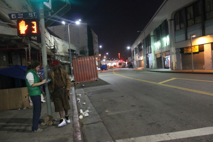 Annabelle Rosborough, 28, surveys Edward Potts, a homeless man who lives on Skid Row during the homeless count in Downtown Los Angeles on January 30, 2013.