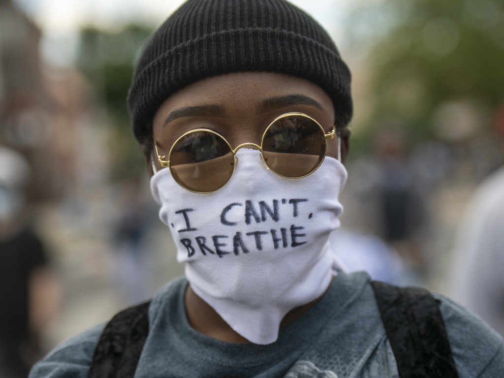 Protests over police treatment of black people have sparked concerns about the spread of COVID-19. Here, a protester marches Monday in Philadelphia with a cloth mask saying,
