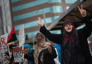 A woman waves to passing motorists at a rally in support of Arab anti-goverment protesters on Saturday afternoon outside the Federal Building on Wilshire Blvd.