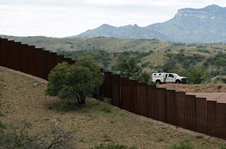 A U.S. Border Patrol vehicle drives along the fence separating the US from Mexico, near the town of Nogales, Sonora, Mexico, on July 31, 2010. Details that have emerged from a forthcoming Senate plan emphasize border security before undocumented immigrants can take steps toward citizenship.