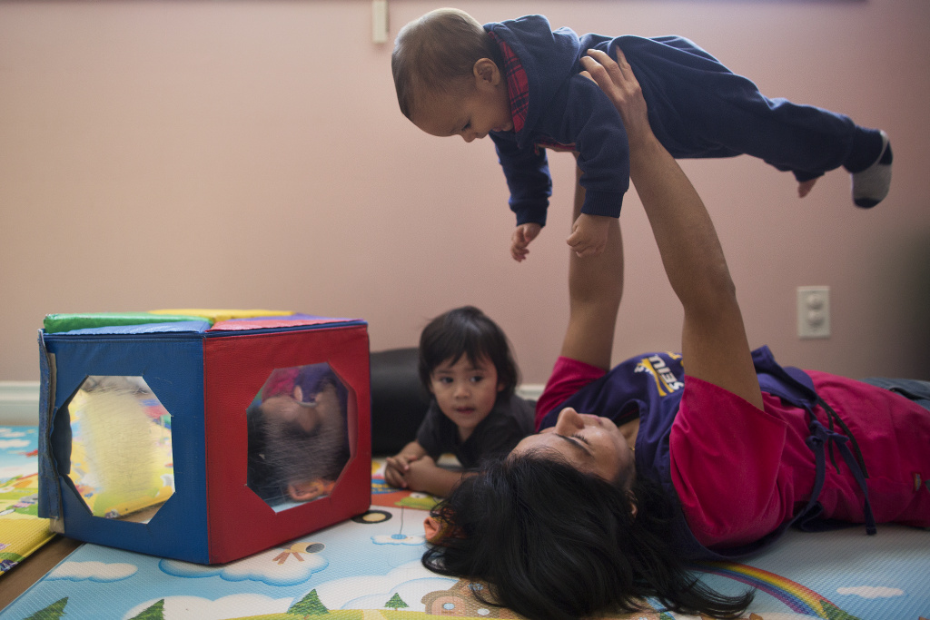 Child care provider Yecenia Rivas plays with children during a yoga session at at Rivas Family Child Care in Reseda on Friday morning, Feb. 13, 2015.