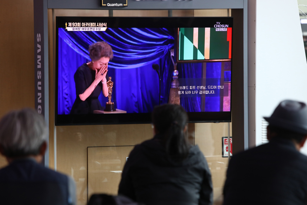 People watch a TV screen showing South Korean actress Youn Yuh-jung at the Seoul Railway Station on April 26, 2021 in Seoul, South Korea.