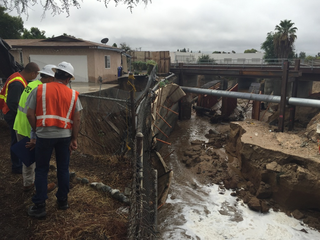 L.A. Public Works officials survey a house in danger of being washed away by rainwater in the city of San Gabriel on Pondosa Avenue during a rainstorm on Tuesday, Sept. 15, 2015.