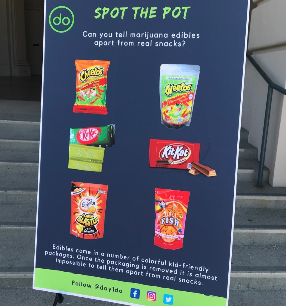 A graphic comparing pot edibles to regular snacks stands on the steps of Pasadena City Hall during an outreach event.