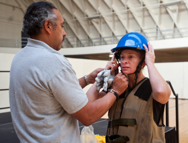Al Perez of the LAFD Legal Liaison Unit helps applicant JJ Edgmon put on a helmet before her first practice try of the Candidate Physical Ability Test.