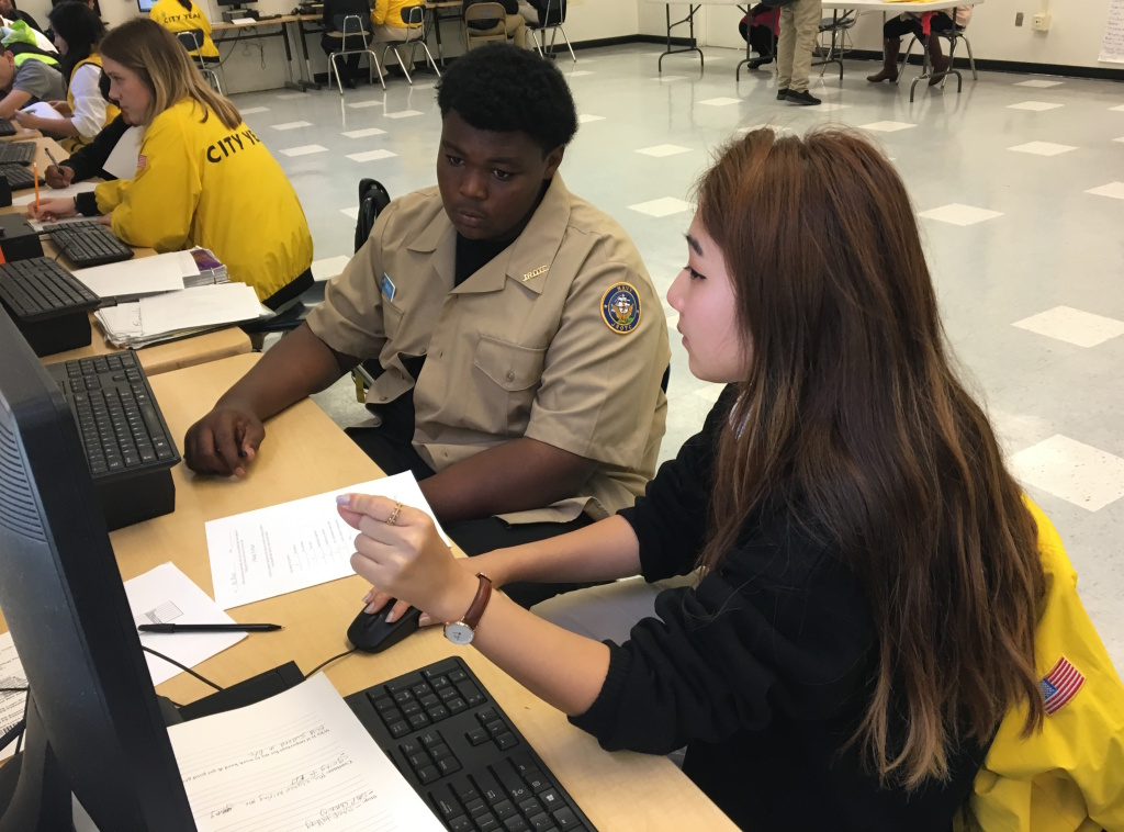 Floyd Maxey (left), a freshman at Alain Leroy Locke College Preparatory Academy, a charter high school in South L.A., goes over his grades with City Year corps member Eleanor Kim.