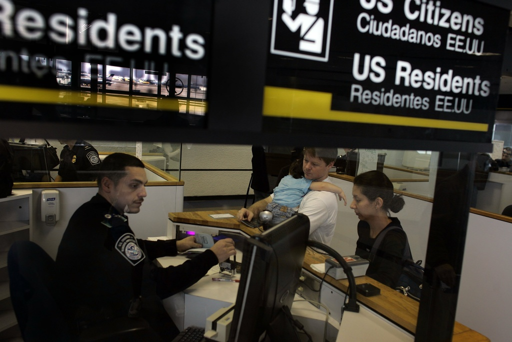 Anthony Ramos, a Customs and Border Protection officer, checks Chris Layman, Katy Layman, 21 months old, and Natalie Layman in at the passport control area