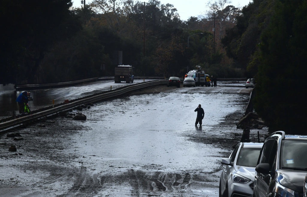 A man wades in a flooded section of the US 101 freeway near the San Ysidro exit in Montecito, California on January 9, 2018.