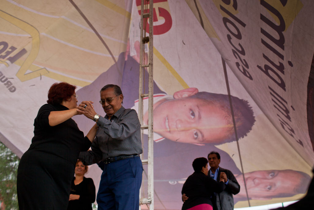 Older couples dance under a massive campaign banner for a political candidate at a campaign rally in the Peñón de Los Baños neighborhood near Juarez Airport.