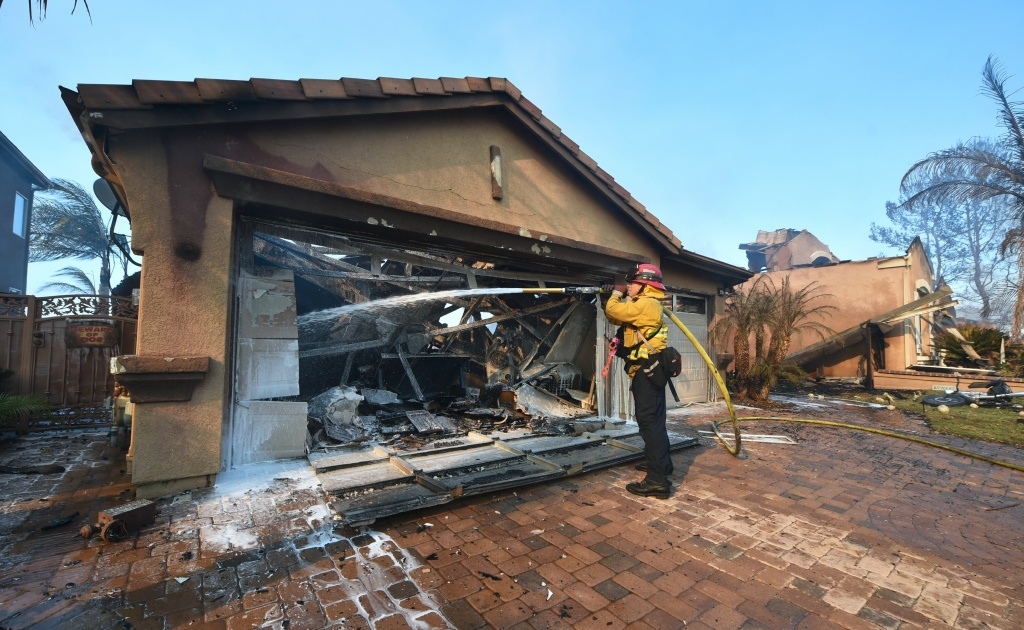 A fireman puts out a fire in a home at an Anaheim Hills neighborhood in Anaheim on Oct. 9, 2017, after a fire spread quickly through the area prompting mandatory evacuations and freeway closures.