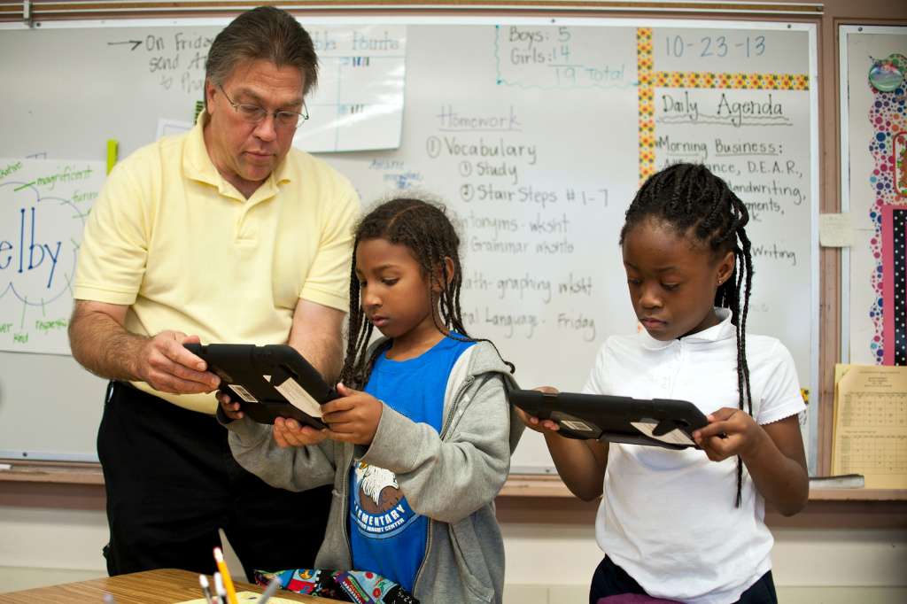Russ Swanson, left, a virtual learning complex facilitator, works with second graders at Baldwin Hills Elementary as they use their iPads for the first time.