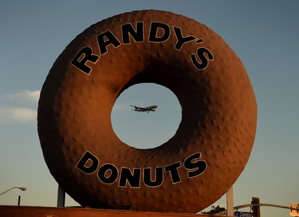A Swissair plane flies past Randy's Donuts which is an iconic landmark in the city of Inglewood, as it makes its descent into Los Angeles International Airport, California on January 24, 2016.  The recent announcement that the St. Louis Rams football team will relocate to a new stadium in Inglewood has started a property boom in the surrounding area.     AFP PHOTO / MARK RALSTON / AFP / MARK RALSTON        (Photo credit should read MARK RALSTON/AFP/Getty Images)
