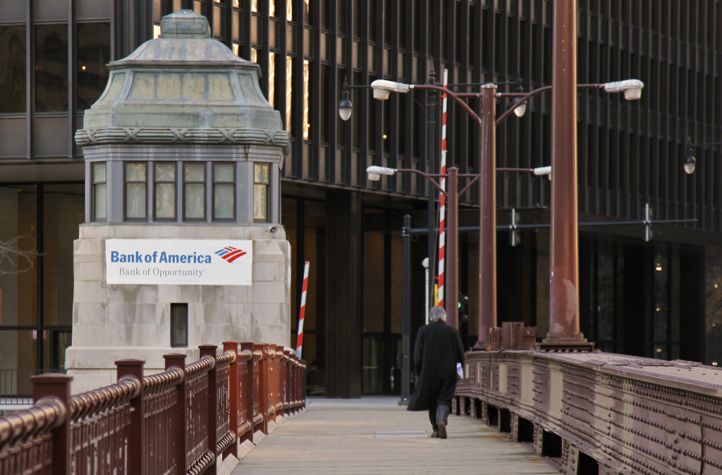 In this photo taken Nov. 17, 2011, a pedestrian walks across a bridge along the Chicago River in downtown Chicago past a bridge house with a Bank of America advertising banner.