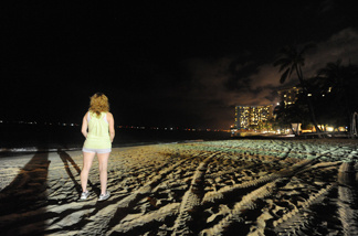A woman watcheds as waves hit the deserted Waikiki shoreline on March 11, 2011 in Honolulu, Hawaii.