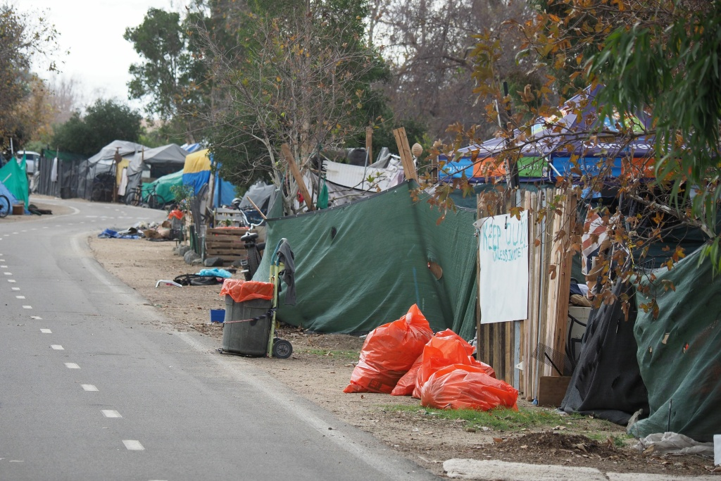 Orange trash bags sit outside tents and tarps of a homeless encampment along the Santa Ana riverbed bicycle path near Angel Stadium in Anaheim, California, January 25, 2018.