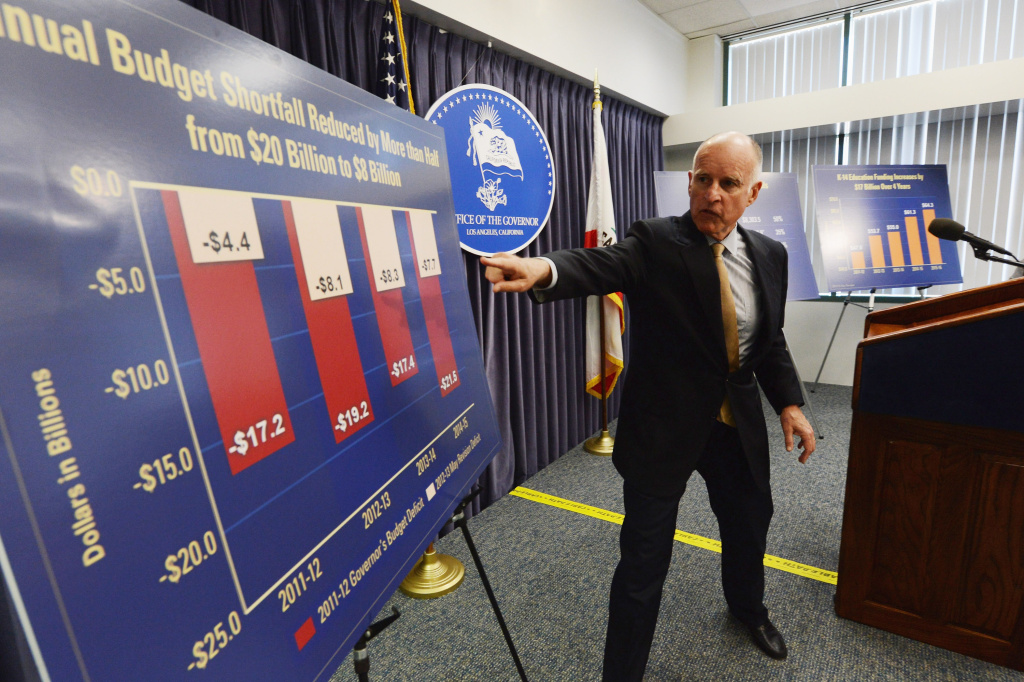 File photo: California Gov. Jerry Brown speaks during a news conference about the state budget on May 14, 2012 in Los Angeles, Calif. What does the revised proposal he signed Wednesday mean for the poor?
