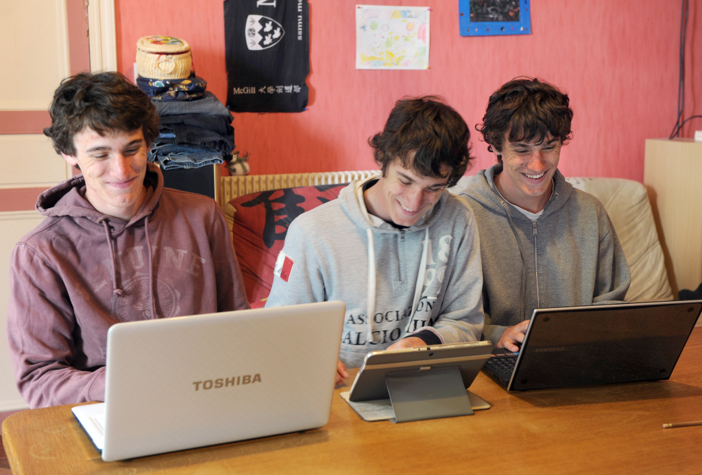 Triplets (L to R) Mickaël, Sylvain and Pascal pose on June 10, 2013 in front of their laptops in their home in Sirac (Gers), southern France.