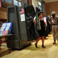 A voter emerges from a manual voting booth after casting her ballot in the mayoral primary election on September 10, 2013 in the Manhattan borough of New York City.