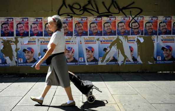 A women passes by in front of propaganda posters of Venezuelan President and candidate Hugo Chavez (top) and opposition presidential candidate Henrique Capriles, in Caracas on October 5, 2012. Elections in Venezuela will be held on October 7.